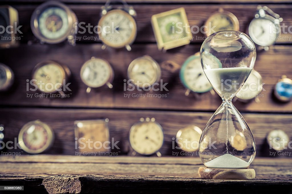 Old hourglass on the background of clocks stock photo