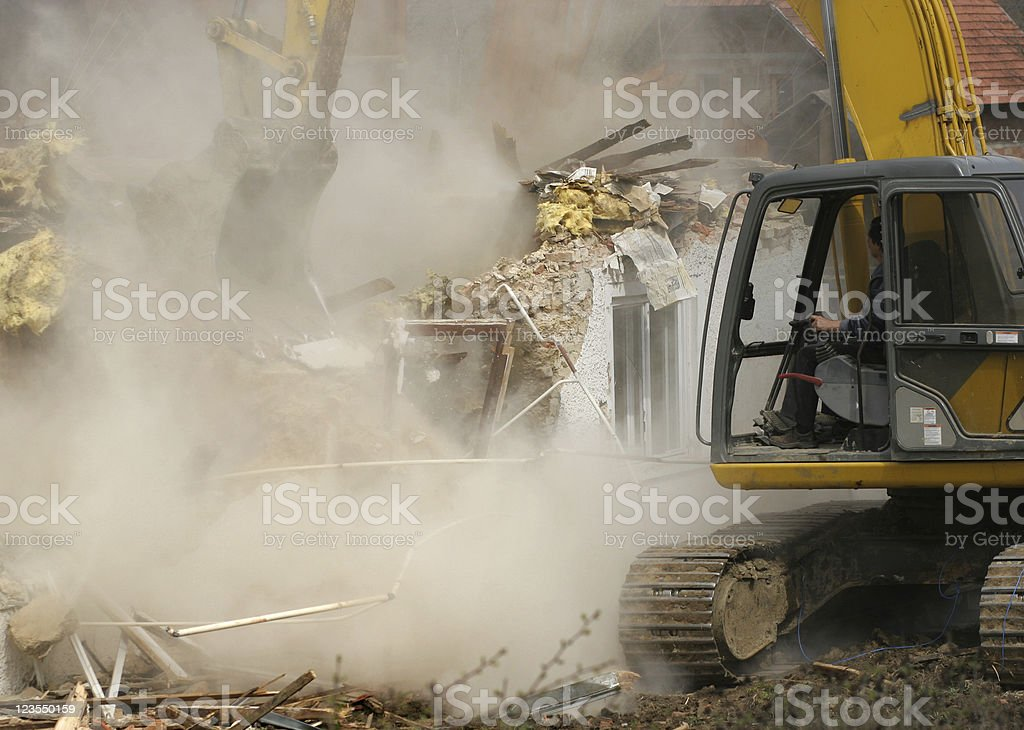 Old house being demolished by a yellow excavator stock photo