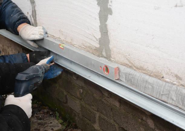 antigua casa de reparación de la pared de la fundación y renovación con la instalación de láminas de metal para impermeabilización y proteja de la lluvia. contratistas con la fundación de reparación. - basement fotografías e imágenes de stock