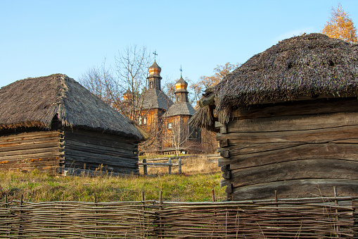 Old house of the peasants with a straw roof and church in the Ukrainian national museum Pirogovo. Kyiv, Ukraine