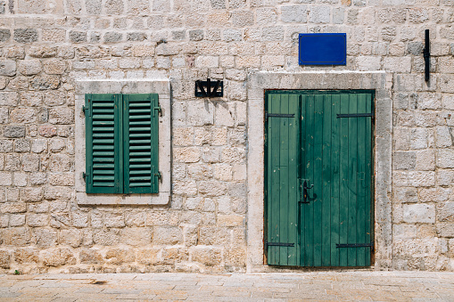 istock Old house, stone wall and wooden door in Kotor, Montenegro 1175815868