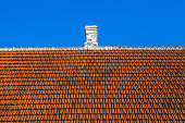 Old house tiled roof with white chimney