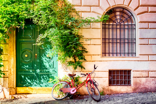 Old house wall in Trastevere, Rome, Italy with a red bicycle and green door. Old cozy street in Rome
