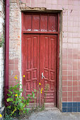 Old house with red high red wooden door