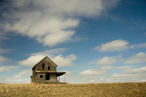 old house on grassy hill with lots of blue sky
