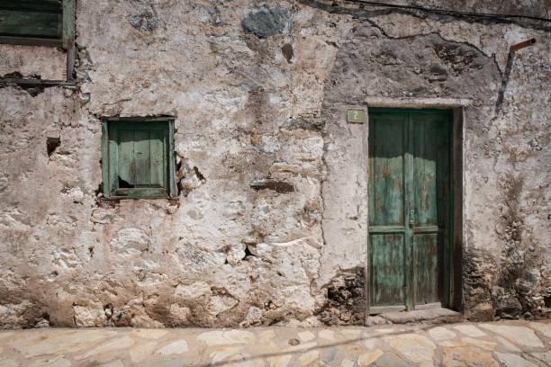Altes Haus mit Holztür und verwitterter Fassade im ländlichen Dorf- – Foto