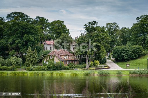 Old houses on the lakeside with reflection in cloudy summer day.  Talsi, Latvia.