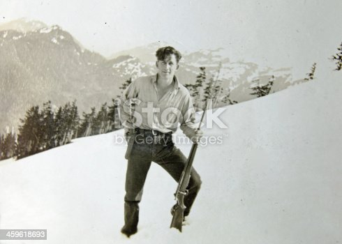An old photograph of a young man with his firearms near Juneau , Alaska... from the early 1930's.