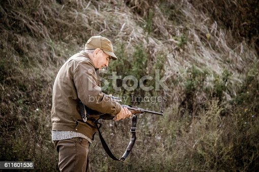658114236 istock photo Old hunter reloads his rifle 611601536