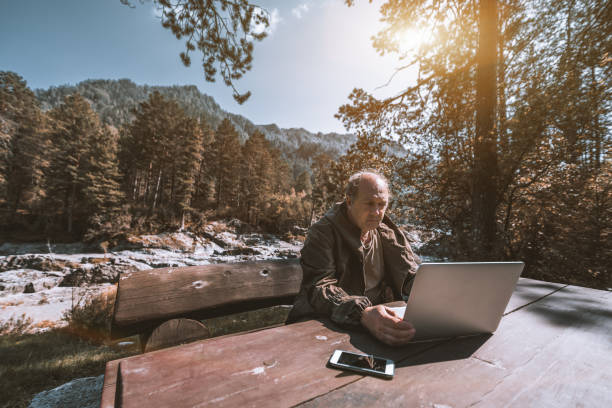 old hunter with his laptop in mountains - altai nature reserve стоковые фото и изображения