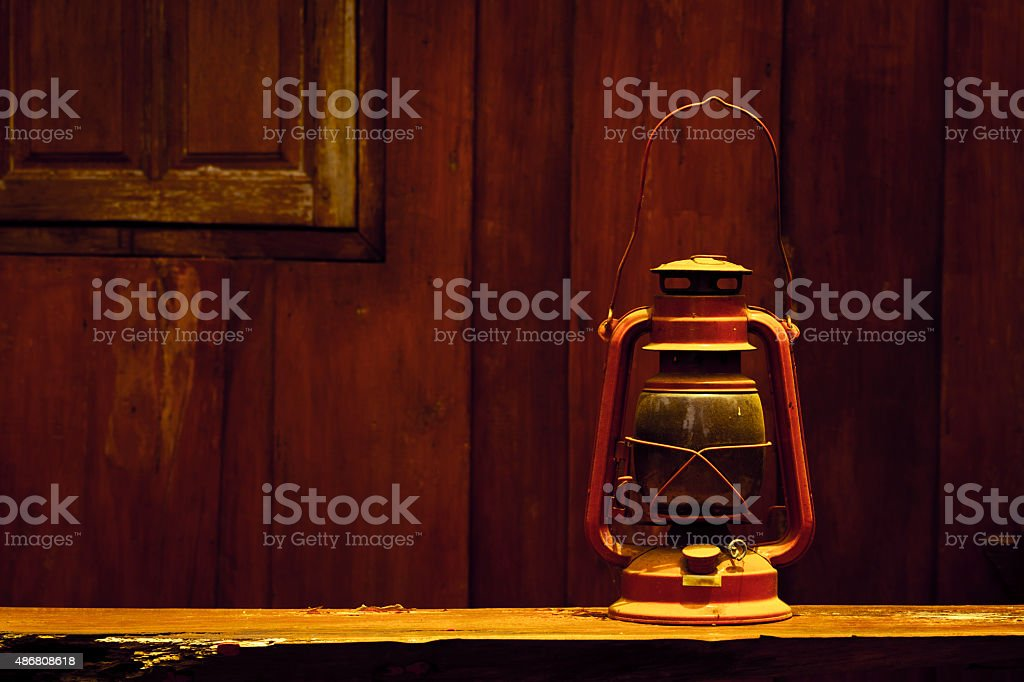 Old hurricane lamp on wooden background in vintage stock photo