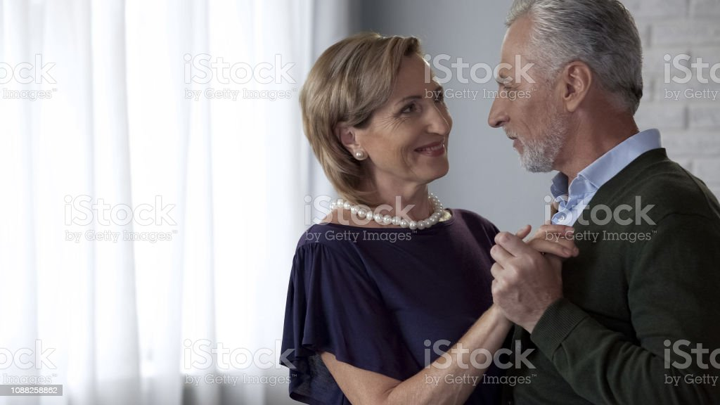 Old husband and wife dancing and tenderly looking at each other,...