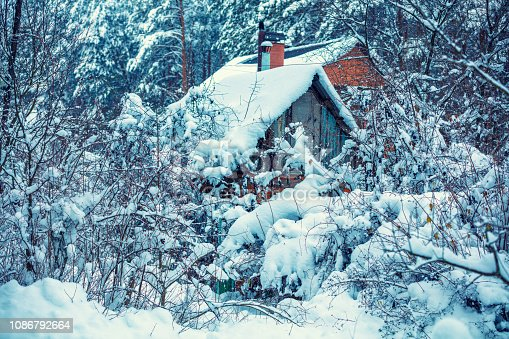 1061644120 istock photo Old hut in the forest. Rural landscape. Forest covered with snow. Snowy winter. Christmas background. Pine trees in snow 1086792664