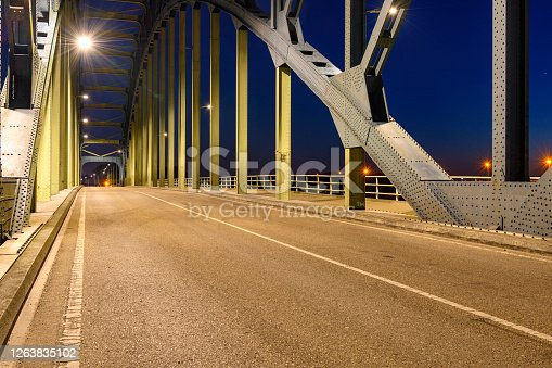 Evening photo of the Old IJsselbrug over the river IJssel between Zwolle and Hattem after sunset. View from the middle of the road on the old steel arch bridge.