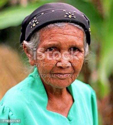 Harau Valley, Indonesia - July 26, 2010. A elderly woman walking along a road poses for a portrait in West Sumatra, Indonesia.