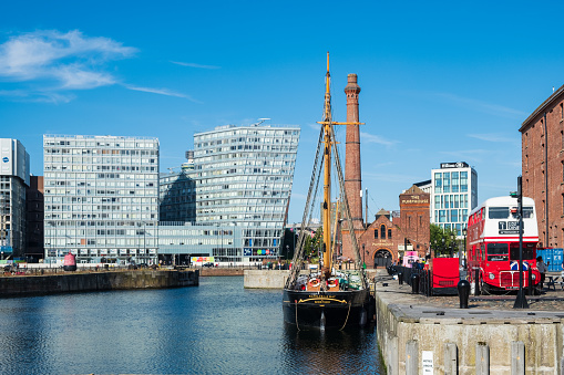 Liverpool, United Kingdom - July 18, 2019: Old industrial warehouses and modern office buildings around the waters of Canning Dock in Liverpool's rennovated docklands