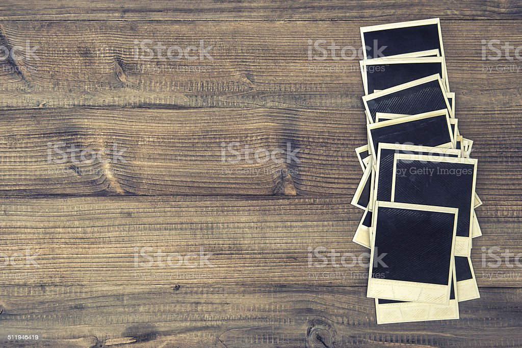 old instant photo frames on rustic wooden background stock photo