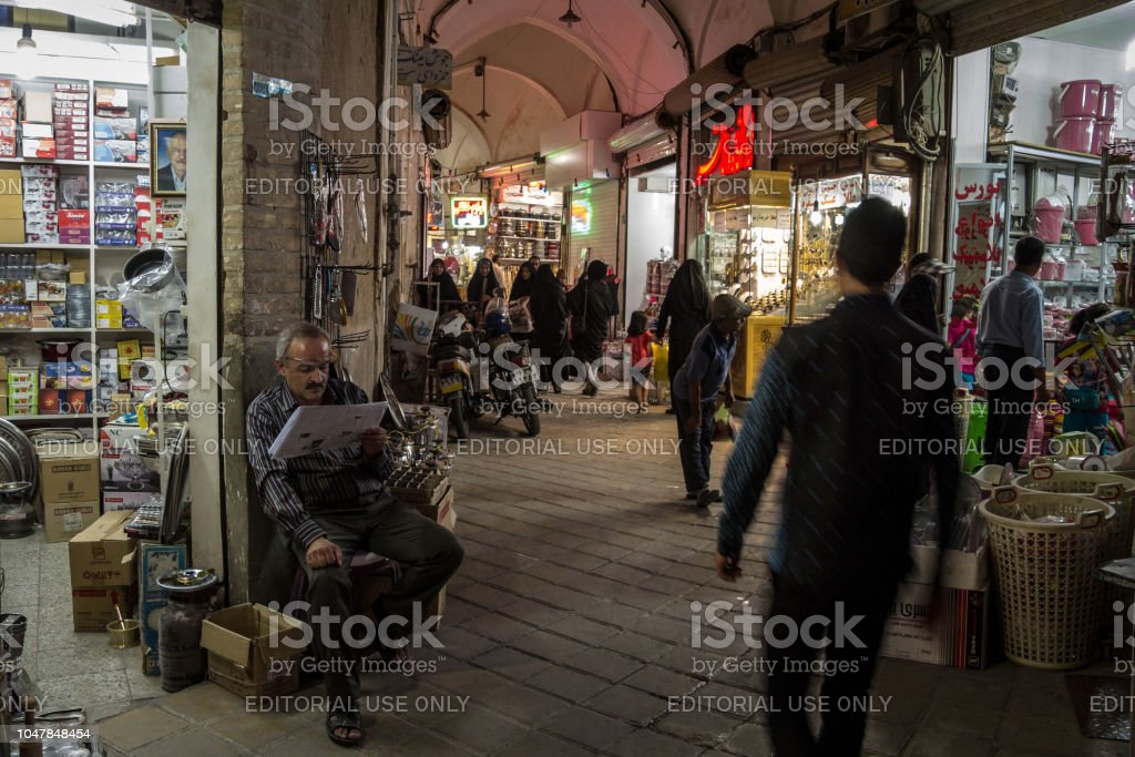 Old Iranian merchant reading newspaper in Farsi in Yazd main bazaar while people are rusing around him. Yazd is one of the main cities of central Iran stock photo