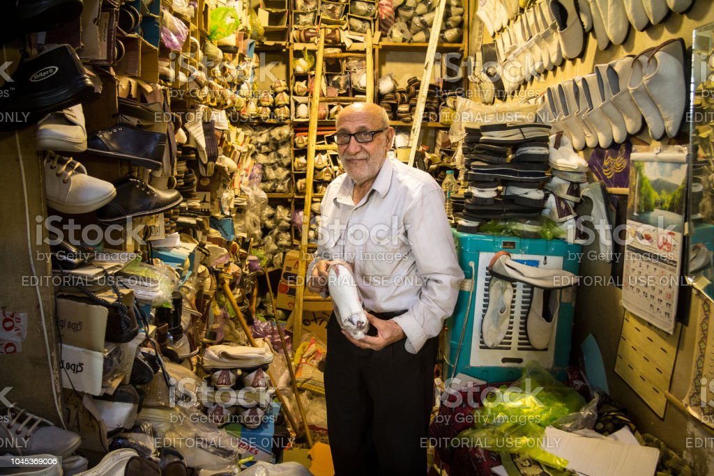 Old Iranian shoemaker showing one of his shoes for sale in his shop in the Isfahan covered bazar market, which is one of the main landmarks of the city stock photo