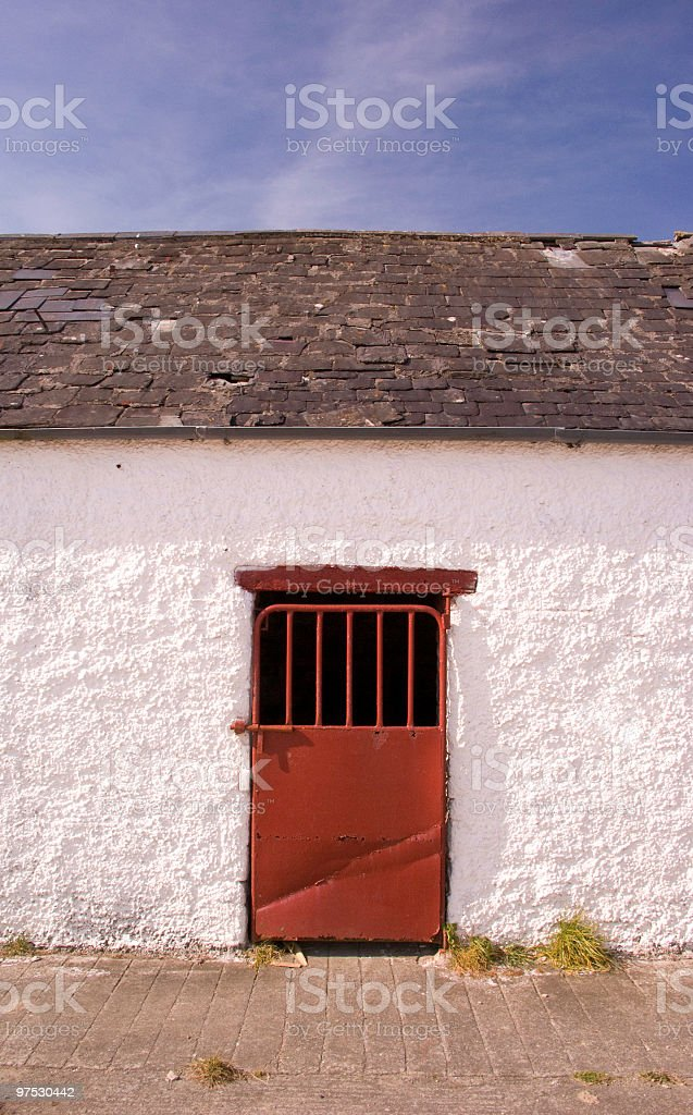 Old Irish farm shed with whitewashed wall and red door royalty-free stock photo