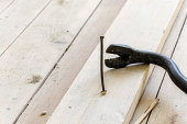 Old iron nail sticking out of floorboards next to a black nail puller. Repair of wooden floors. Close-up.