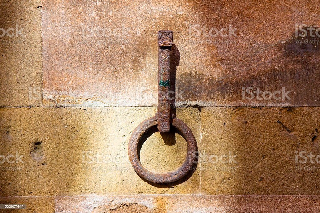 Old iron ring fixed to a stone wall stock photo