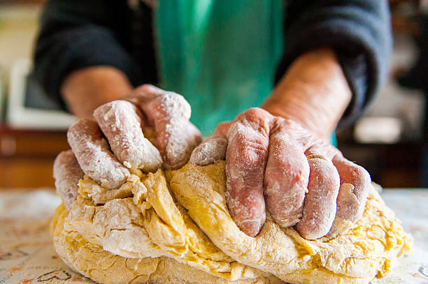 old italian  lady's hands preparing home made italian pasta stock photo