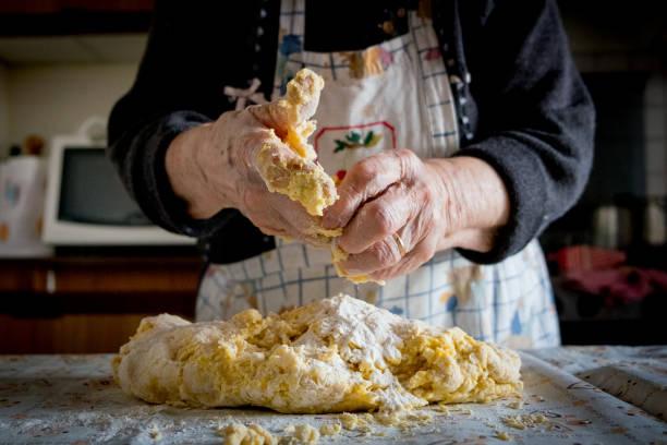 old italian lady's making home made italian pasta stock photo