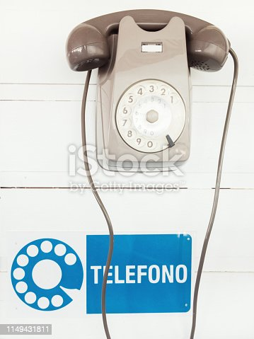 old Italian rotary telephone hanging from a wall with a sign that says