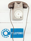old Italian rotary telephone hanging from a wall with a sign that says \