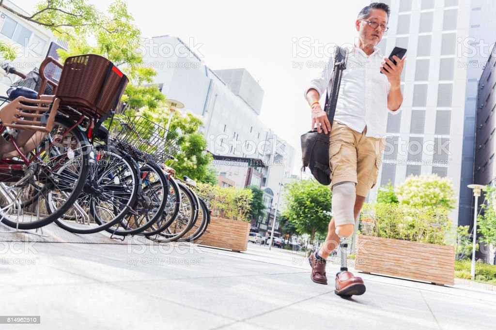 Old Japanese man walking in downtown while using his instant messaging app on a smart phone stock photo
