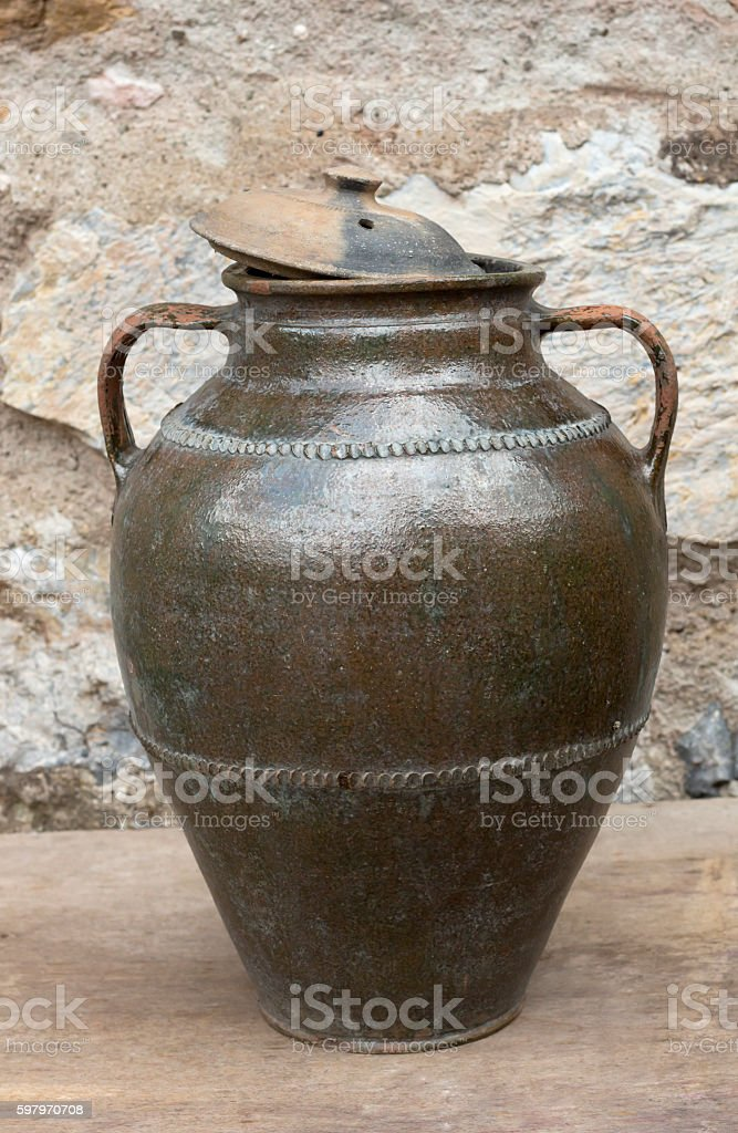 Old jar on the wooden board with stones in the background stock photo
