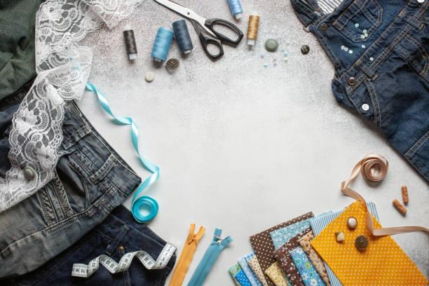 Alte Jeans und Stoffstücke mit Nähaccessoires. Ansicht von oben. Upcycle-Konzept. – Foto