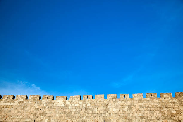 Old Jerusalem City Wall The surrounding wall of the old city of Jerusalem beneath a spectacular cloudy blue sky. jerusalem old city stock pictures, royalty-free photos & images