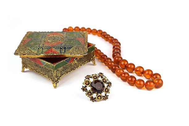 alte schmuck-box, perlen und vintage-brosche bernstein-halskette - altes schmuckkunsthandwerk stock-fotos und bilder