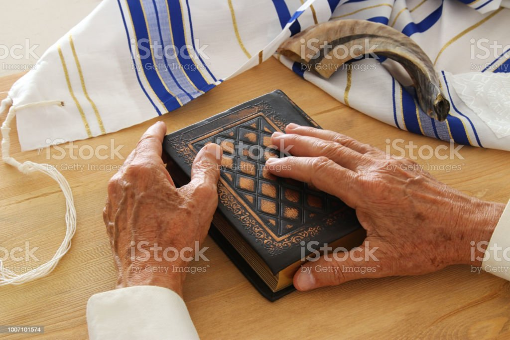 Old Jewish Man Hands Holding A Prayer Book Praying Next To Tallit