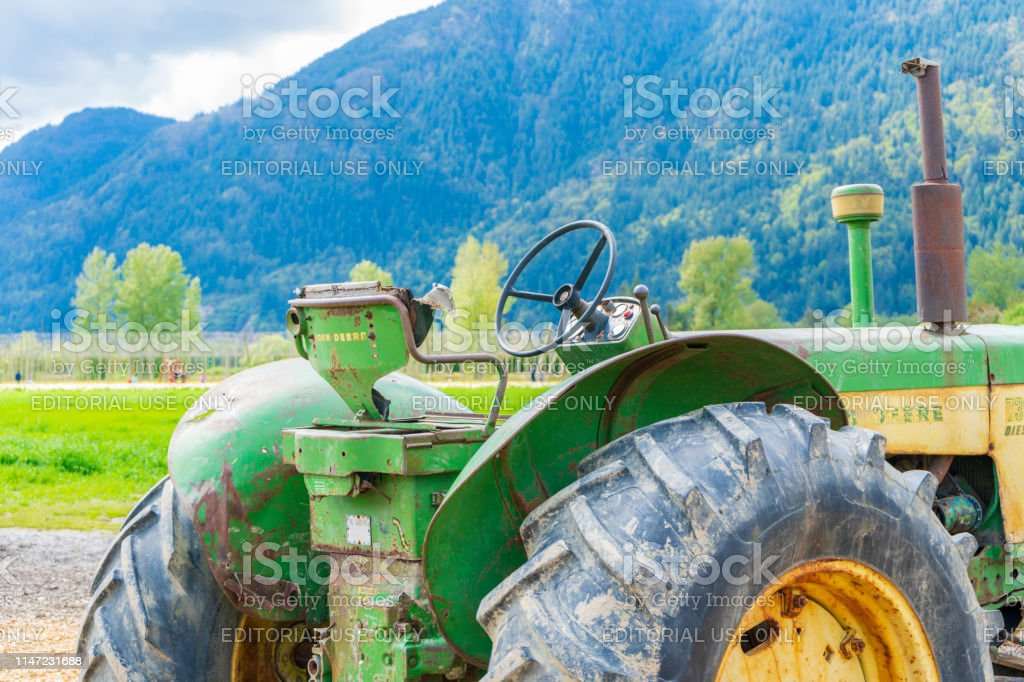 Old John Deere Tractor With Rusty Dirty Machine Parts Sitting On A