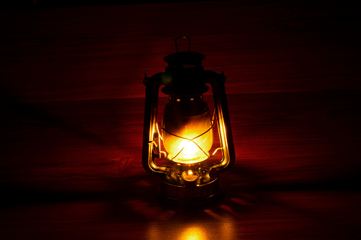 old kerosene lamp glows in a dark place against the shadows and wooden background.