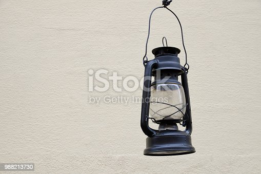 Old kerosene lamp on the background light walls. Space for text