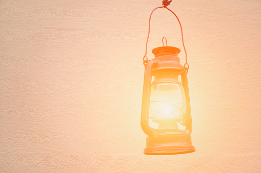 istock Old kerosene lamp on the background walls. Space for text 988213870
