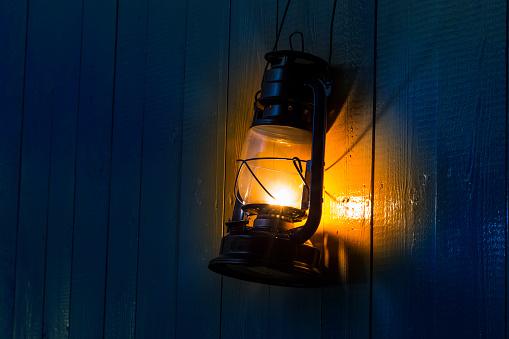old kerosene lantern hanging on the yellow wooden wall