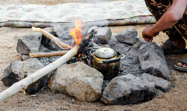 old kettle by the fire and people sitting next in Egypt Dahab South Sinai stock photo