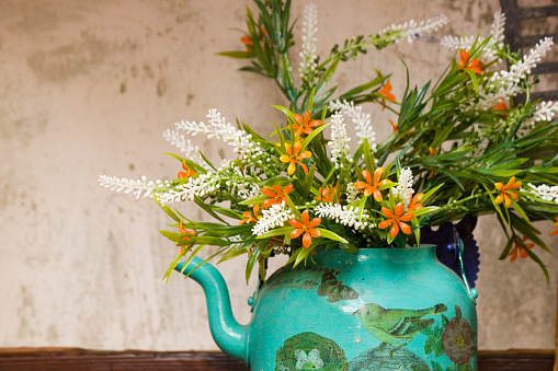 old kettle decorated and used as a vase for flowers