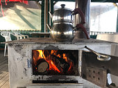 Old kettle on traditional indoor fireplace
