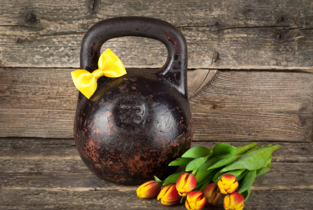 old kettlebell with a yellow tied bow on a wooden background, gentleman concept - number 23 stock photos and pictures