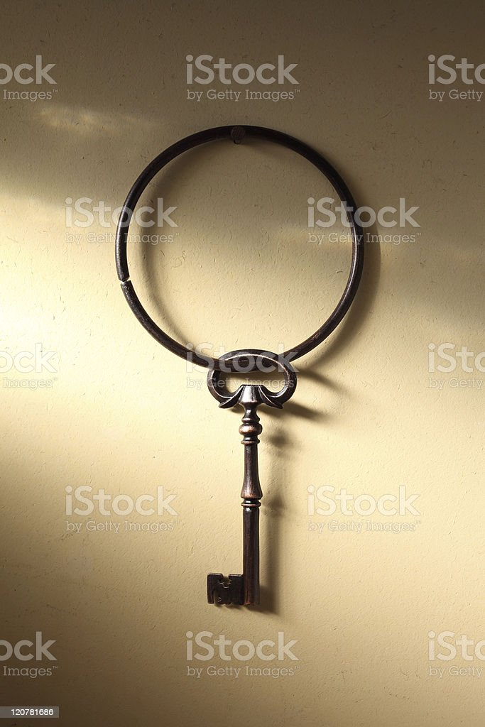 Old key hanging on a wall royalty-free stock photo