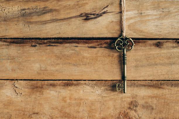alter schlüssel hängen, dunkelbraunem holz mit platz. - schlüssel dekorationen stock-fotos und bilder