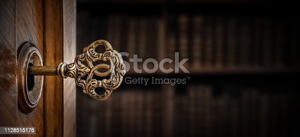 istock Old key in keyhole, macro shot. Retro style. Concept and Idea for History, business, security background. 1128515175