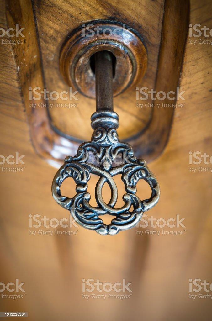 Old key in keyhole, macro shot. Retro style. stock photo