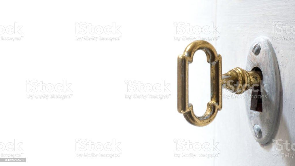 Old key in keyhole, macro shot, white background. stock photo